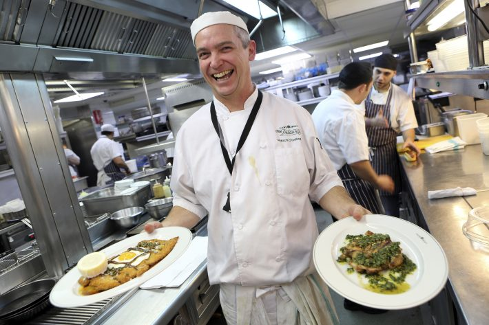 A chef with schnitzel and spatchcocked chicken dishes at The Delaunay restaurant.